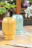 A DIY shot of hand painted marinade mason jars and brush Royalty Free Stock Images