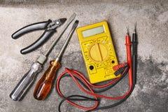 DIY si dirigono gli attrezzi, i cacciaviti, le pinze ed il multimetro dell'elettricità sul fondo del cemento fotografie stock libere da diritti