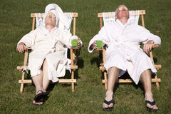 Do-It-Yourself Spa Day. Mature couple detoxing in lounge chairs during a do it yourself spa day in their backyard dressed in bathrobes with cucumber covering Royalty Free Stock Images