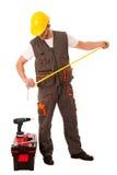 DIY - ung man som mäter med metern som utrustas med verktygslådan och b Royaltyfri Fotografi