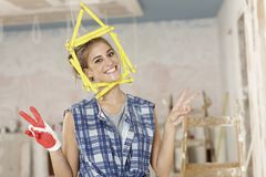 DIY woman. Happy woman building a new home, DIY, little house made of ruler framing her face royalty free stock photography
