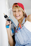DIY woman. Woman in front of ladder with powertool and a range of tools in her pocket Stock Images