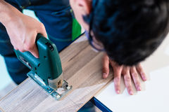 DIY worker cutting wooden panel with jig saw Stock Photos