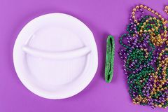 DIY wreath Mardi Gras, Fat Tuesday purple background. Gift idea, decor Mardi Gras. Wreath plastic plates, satin ribbon, green, yellow, purple bead. Step by stock photos