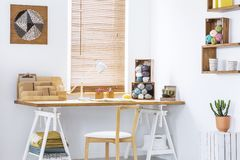 DIY yarn art on a white wall of a scandinavian crafts room interior and creative workspace with knitting tools. Real photo. stock photography