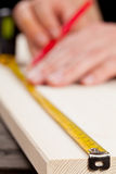 DIY. Young man measuring wooden plank - diy or home renovation concept royalty free stock photo