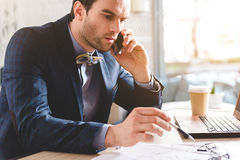 Dizer masculino perturbado no telefone celular no escritório fotografia de stock