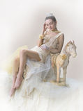 Dizziness. Gentle dreamy image of a teenage girl in a nightgown, sidyashey next to toy horse. The girl is experiencing a slight in vintage aesthetics with Royalty Free Stock Photo