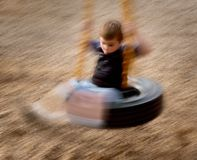 Dizzy. Young boy on tire swing twirling Royalty Free Stock Images