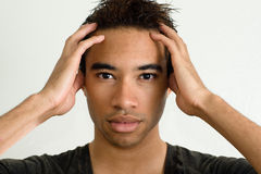 Dizzy head. A young african american male holds his head to keep things straight Stock Image
