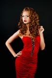 Djärv rödhårig flicka i en röd klänning Royaltyfria Foton
