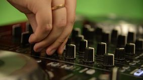 DJ在搅拌器,DJ控制器后站立,混合音乐,扭转杠杆,射击手特写镜头 股票视频