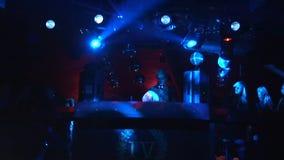 Dj执行在拥挤夜总会阶段的转盘  蓝色激光束 放大 影视素材