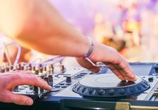 Dj混合在海滩党节日的与跳舞在背景中的人-演奏音乐搅拌器音频室外的节目播音员 免版税图库摄影