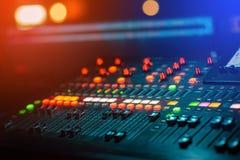 DJ音乐搅拌器混合的控制台在控制与bokeh的声音的夜总会 免版税库存图片