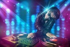 DJ που αναμιγνύει τη μουσική σε μια λέσχη με τα μπλε και πορφυρά φω'τα Στοκ Εικόνα
