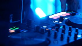 DJ που αναμιγνύει τη μουσική στην κονσόλα στο νυχτερινό κέντρο διασκέδασης απόθεμα βίντεο