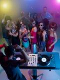 DJ που αναμιγνύει τη μουσική στο συμβαλλόμενο μέρος με τους χορεύοντας ανθρώπους Στοκ εικόνες με δικαίωμα ελεύθερης χρήσης