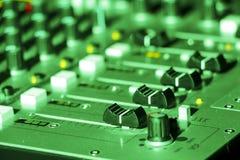 DJ που αναμιγνύει το γραφείο κάτω από το πράσινο φως Στοκ Φωτογραφίες