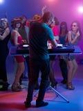 DJ που στέκεται και που αναμιγνύει τη μουσική στο συμβαλλόμενο μέρος Στοκ Εικόνες