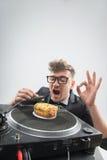 DJ που τρώει doughnut στην περιστροφική πλάκα θέσεων εργασίας Στοκ Φωτογραφίες
