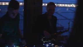 DJ στην περιστροφική πλάκα Saxophone παιχνιδιού ατόμων Κόμμα στο νυχτερινό κέντρο διασκέδασης Σκιαγραφίες μουσικοί απόθεμα βίντεο