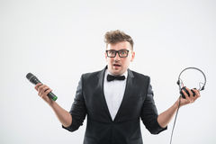 DJ στο μικρόφωνο και τα ακουστικά εκμετάλλευσης σμόκιν Στοκ Εικόνες
