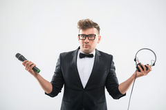 DJ στο μικρόφωνο και τα ακουστικά εκμετάλλευσης σμόκιν Στοκ Φωτογραφία