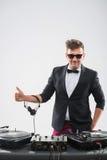 DJ στο σμόκιν που παρουσιάζει αντίχειρά του που αναμένει επάνω Στοκ εικόνα με δικαίωμα ελεύθερης χρήσης