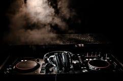 DJ закручивая, смешивая, и царапая в ночном клубе, руках управлений следа фишки dj различных на палубе dj, светах строба и тумане Стоковые Изображения