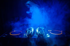 DJ закручивая, смешивая, и царапая в ночном клубе, руках управлений следа фишки dj различных на палубе dj, светах строба и тумане Стоковая Фотография