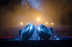DJ закручивая, смешивая, и царапая в ночном клубе, руках управлений следа фишки dj различных на палубе dj, светах строба и тумане Стоковое Изображение