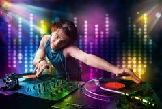 Dj играя песни в диско с светлой выставкой стоковое фото