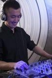 演奏音乐的一个年轻男性DJ的画象在夜总会 库存图片