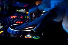 混合和抓音乐的DJ在音乐会 免版税图库摄影