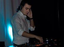 在他的甲板的英俊的DJ混合的音乐 库存图片