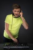 DJ aan het werk dat op donkere grijze achtergrond wordt geïsoleerd Stock Fotografie