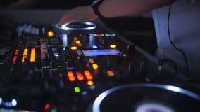 DJ achter de console, op stadium, die sporen in de strobing en opvlammende lichten van de atmosferische danspartij mengen stock footage