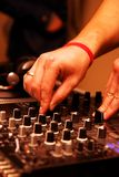 DJ adjusting music level on mixer Royalty Free Stock Image