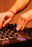 DJ adjusting sound level on mixer Royalty Free Stock Photography