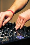 DJ adjusting sound level on mixer Royalty Free Stock Images