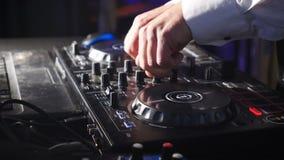DJ atr?s do console, na fase, em trilhas de mistura no efeito estrobosc?pico atmosf?rico do dance party e em luzes de piscamento  vídeos de arquivo