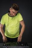 DJ bei der Arbeit lokalisiert auf dunkelgrauem Hintergrund Lizenzfreie Stockfotografie