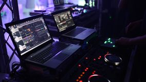 DJ bij de disco werkt achter de afstandsbediening Dansvloer en lichte muziek stock videobeelden