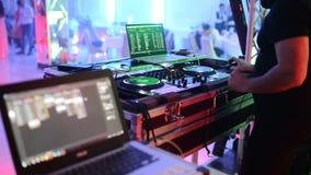 DJ bij de disco werkt achter de afstandsbediening Dansvloer en lichte muziek stock video