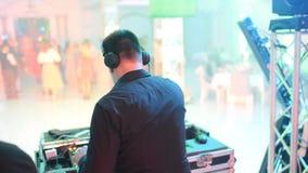 DJ bij de disco werkt achter de afstandsbediening Dansvloer en lichte muziek stock footage