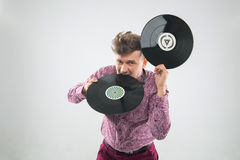 DJ biting vinyl record. Top view closeup portrait of excited young DJ with stylish haircut, bow tie having fun with vinyl record biting it isolated on white royalty free stock photos