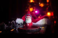 Dj-blandare med hörlurar på mörk nattklubbbakgrund med helgdagsafton för nytt år för julgran Stäng sig upp sikt av beståndsdelar  Arkivfoton