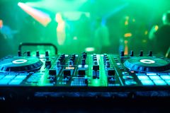 DJ booth at night club party for music mixing with green blurred background. DJ booth at a night club party for music mixing with green blurred background Stock Photo