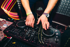 DJ brings music and turns volume on musical equipment Royalty Free Stock Photo